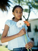 Girl 12_13 holding two flowers outdoors,portrait,waist up