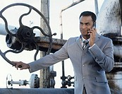 Business man talking on mobile phone,leaning on oil refinery valve