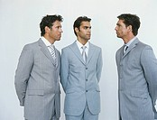 Three business men in suits looking at each other,three quarter length