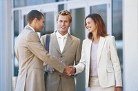 Businessman and woman shaking hands, smiling
