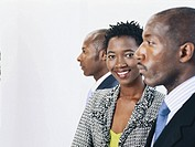Businesspeople standing in row, businesswoman smiling