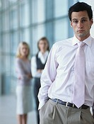 Business man leaning against wall,colleagues standing in background