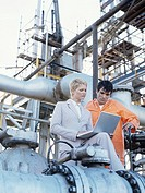 Business woman and oil refinery worker using laptop,piping and valve in foreground