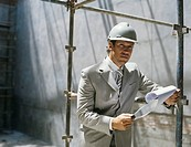 Business man in hard hat holding clipboard on construction site,portrait