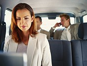 Young businesswoman sitting in car using laptop with businessmen sitting behind