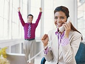 Businesswoman using landline phone, man standing with hand raised in background