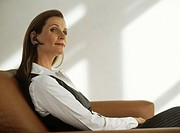 Businesswoman with hands free device sitting in armchair