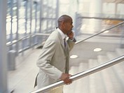 Businessman using mobile phone while climbing steps, side view
