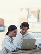 Businessman and woman standing at docks, using laptop