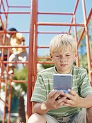 Children on climbing frame, focus on boy 6_9 playing game console in foreground