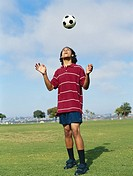 Young man heading soccer ball, low angle view