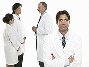 Group of doctors, three talking, one looking at camera, on white background
