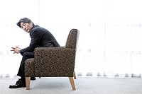 Businessman sitting in armchair, side view