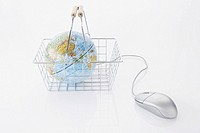 still life of globe in shopping basket and computer mouse