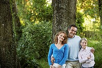 Young girl with parents leaning on tree in park portrait (thumbnail)