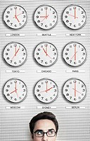 Office worker in front of clocks showing time across the world