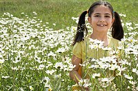 Girl 7_9 holding flowers in meadow portrait