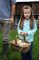 Girl 5_6 holding egg basket father low section standing nearby outdoors portrait