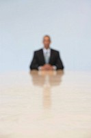 Business man sitting at end of conference table defocused