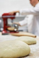 Chef using dough mixer in kitchen focus on dough in foreground
