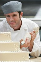 Male chef icing wedding cake in kitchen (thumbnail)