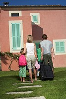 Family with three children 6_11 entering house with luggage back view