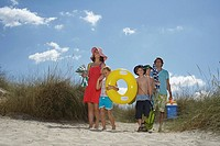 Parents with three children 6_12 carrying beach accessories