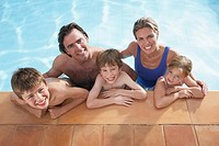 Portrait of family with three children 5-11 in swimming pool smiling (thumbnail)