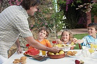 Father serving slices of pineapple to children 6_11 sitting at outdoor table