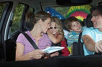 Family with two children 5-6 in car interior talking (thumbnail)