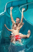 Father and son 7_9 with arms outstretched on water slide