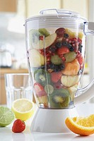 Blender filled with fresh fruits close_up