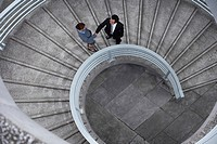 China Hong Kong two business people shaking hands standing on spiral staircase view from above