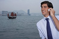 Young business man talking on mobile traditional Chinese junk boat in background