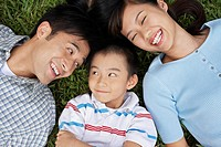 Couple with son 7-9 lying on grass portrait elevated view (thumbnail)