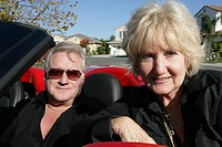 Mature couple looking at camera in a car