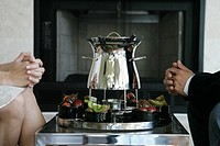 Couple sitting in front of a fondue pot