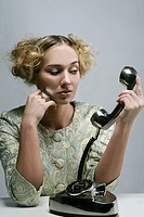 Woman looking at a phone receiver