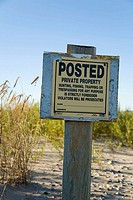 Posted private property, no trespassing sign on beachfront property, Lake Michigan shoreline, grasses growing in sand  Racine, Wisconsin, USA