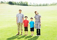 Family standing in the field of grass