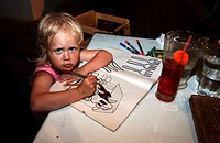 Three year old girl drawing at the dinner table while waiting for the food to come