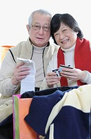 Senior asian couple shopping according to their budget