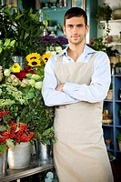 Male florist standing amongst the flowers in his shop