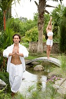 Portrait of an adult couple practicing yoga in a tropical garden