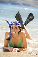 A woman wearing snorkeling equipment lying on a beach