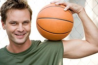 Man in a green vest holding a basketball