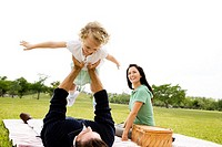 Father lifting up daughter on picnic rug