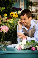 Male florist at the shop counter, taking an order over the telephone