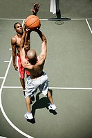 Two men playing on an outdoor basketball court