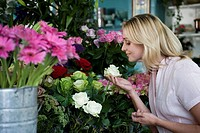 Woman in a florist's shop, smelling a white rose